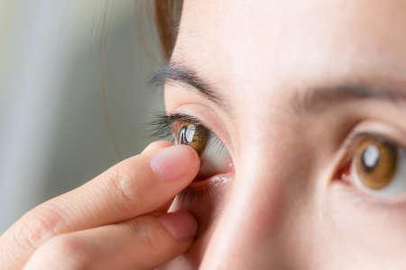 Photo pour Close-up shot of young woman wearing or remove contact lens. - image libre de droit