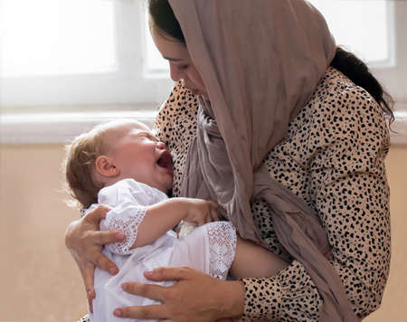 Photo pour Cute crying baby girl dressed in white in the arms of her mother wearing shawl - image libre de droit