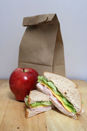 a brown bag lunch with an apple, sandwich and brown bag