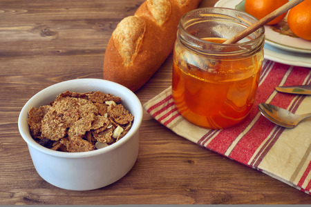 breakfast with honey, oranges, cornflakes on a rustic wooden table