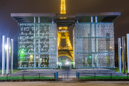 PARIS,FRANCE-NOVEMBER 16:  The Eiffel Tower at Dusk looking through the Mur de la Paix Wall for Peaceon the 16 november 2009, in Paris,France. The wall consists of 12 glass panels where the word PEACE is written in 32 languages.