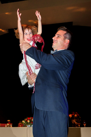 A little flower girl dances with her father at a wedding reception.  She has her hands in the air as swings her around.