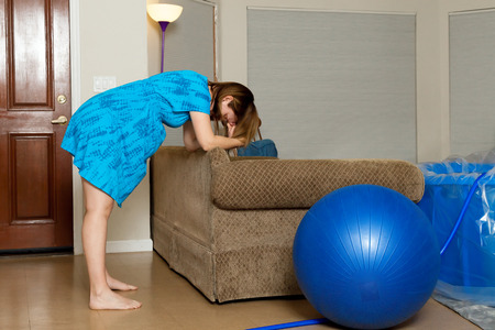 Photo pour A woman in labor leans forward onto the back of a couch as she breathes through a contraction.  There is a birthing ball and a birthing tub in the room. - image libre de droit