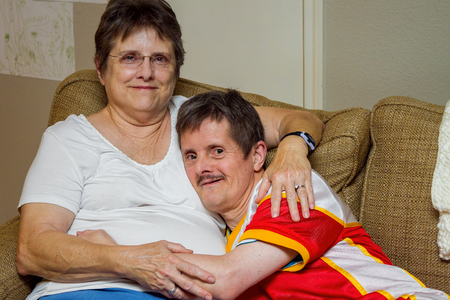 Photo for An older man with Downs Syndrome, hugs his older sister as they sit on a couch. The woman looks tired, the man looks mischeivious.  He is about to tickle her. - Royalty Free Image