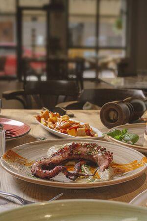Photo pour Grilled fish dish and tapas on the restaurant table. - image libre de droit