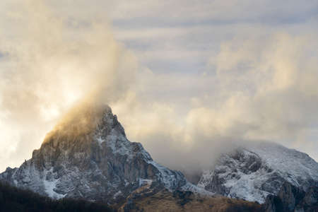 Clouds and fog are caressing the mountain peaks.