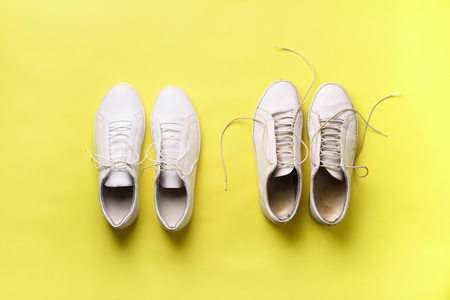 Photo pour Old dirty sneakers vs new white sneakers on yellow background. Trendy footwear. Top view. Concept of experience, discipline and chaos, accuracy \ mess, stylish shoes. Back to school. - image libre de droit