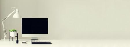 Photo pour Designer workspace. Banner. Minimalistic home office. Blank screen desktop computer. Mockup desktop computer, lamp, graphics tablet, keyboard, mouse, pen, succulent plant on white desk. Copy space. - image libre de droit