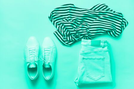 Photo pour Female white sneakers and jeans, striped t-shirt on mint color background with copy space. Top view. Summer fashion, capsule wardrobe concept. Biscay Green color of the year 2020 - image libre de droit