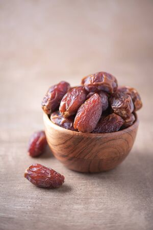 Photo for Dried date fruit in wooden bowl on wood textured background. Copy space. Superfood, vegan, vegetarian food concept. Macro of dates texture, selective focus. Healthy snack - Royalty Free Image
