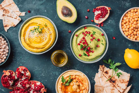 Photo pour Bowls with yellow hummus and green hummus, tahini, olive oil, sesame seeds, pita, raw chickpeas, avocado, pomegranate on dark background. Middle eastern, jewish, arabic cuisine. Top view - image libre de droit