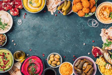 Photo pour Traditional Middle Eastern assorted meze: hummus, pita, olives, pistachios, dolma, falafel balls, pickles, babaganush, vegetables, pomegranate, eggplants. Top view. Banner. Copy space. Arab meal - image libre de droit
