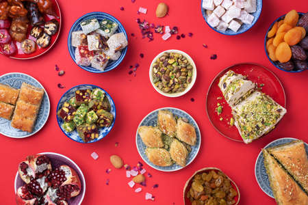 Photo for Traditional turkish delight on red background. Top view. Flat lay. Copy space. Arab dessert, baklava, halva, rahat lokum, sherbet, nuts, pistachios, dates, raisins, dried apricots, churchkhela. - Royalty Free Image