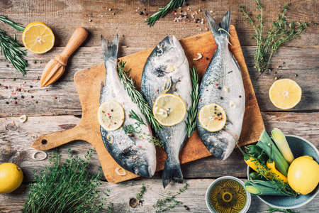 Photo pour Raw dorado fish with ingredients, lemon, herbs, oil, vegetables and spices on wooden cutting board over wood background. Top view. Healthy food diet. Food pattern. Seafood concept. - image libre de droit