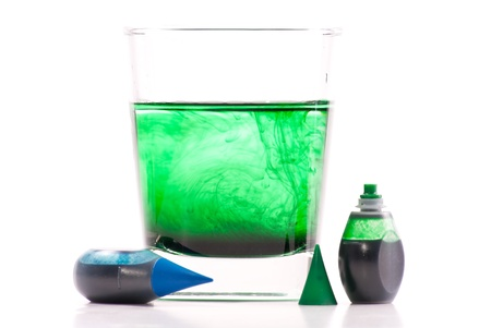 Green Food Coloring Swirling in Glass of Water