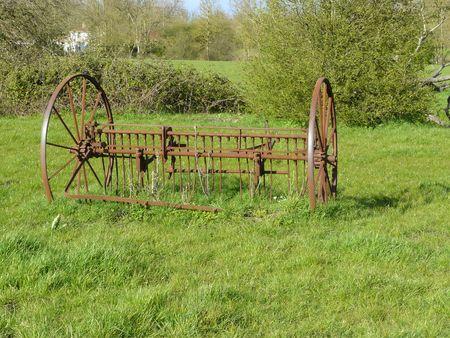 Roues de machine agricole ancienne avec rateau, sur un pré