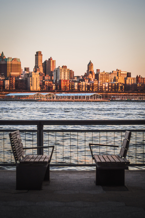 Photo for Landscape of benches on the Manhattan Shores Facing Brooklyn Heights Separated by the East River - Royalty Free Image