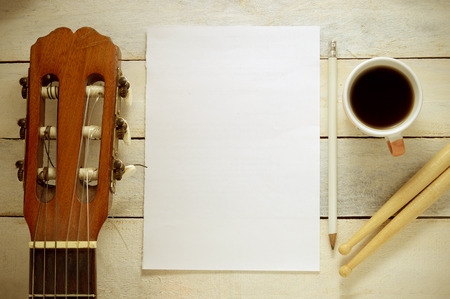 Inspirational background with a Spanish classical guitar on a wooden table while composing. Score sheet a pencil and a cup of coffee for the music composer