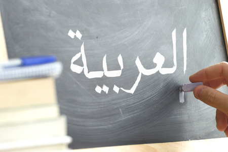 Hand writing on a blackboard in an Arabic class. Some books and school materials.
