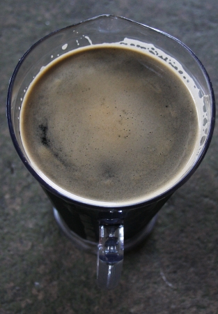 Looking down at a pitcher of dark beer