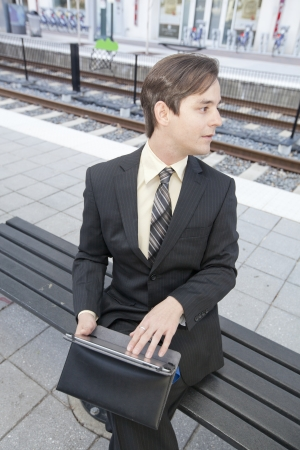 A young businessman using a mobile tablet sitting at a train station