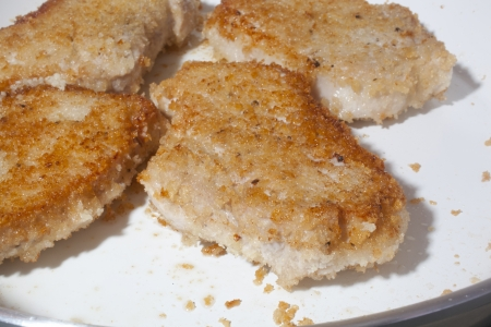 Browning breaded pork chops on a ceramic skillet.