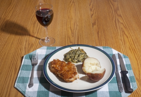 A dinner plate of breaded Pork chop, baked potato and spinach pie, on a table with a glass of red wine.