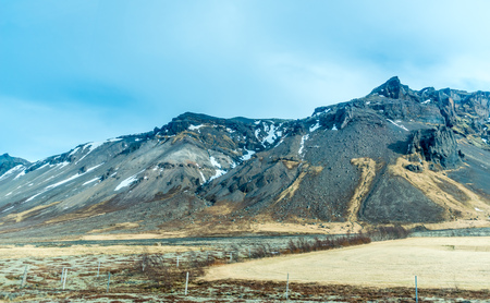 Mountains, valleys and volcano around entrance of ice cave in winter season, very famous landmark in Iceland travel