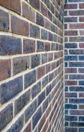 Vertical shot of a brick wall with a corner at the back of the picture.  Red and purple bricks with white mortar pointing.