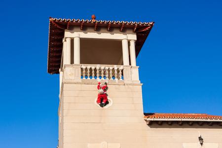 Santa Claus (Papa Noel) climbing up the wall. Palma, Majorca, Spain