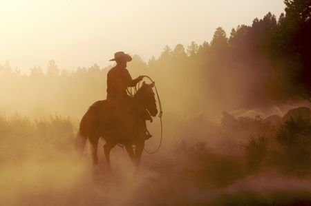 Cowboy outside in the setting sun