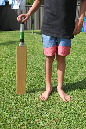A boy standing holding a cricket bat in a surburban backyard. Backyard cricket is an Australian backyard summer classic activity.