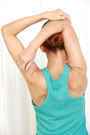 young woman doing self shoulder stretch