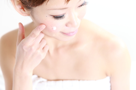 young Japanese woman applying cream on her faceの写真素材