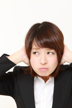 Young Japanese businesswoman suffers from noise
