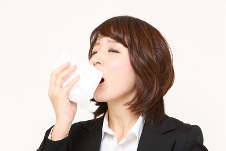 businesswoman with a allergy sneezing into tissue
