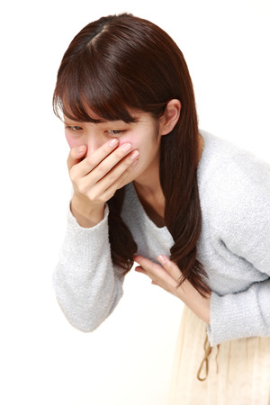 portrait of young Japanese woman vomit