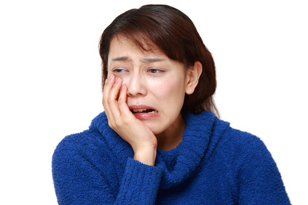 asian woman suffers from toothache