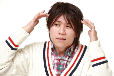 young Japanese man suffers from headache