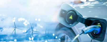 Photo pour Double exposure of EV electric car charge battery uses nature electric energy from wind turbine to generate electricity. Bokeh light blue sky panoramic banner background copy space. Green eco concept. - image libre de droit