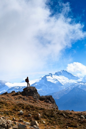 A woman is standing on a rock overlooking  the canadian rocky mountains.