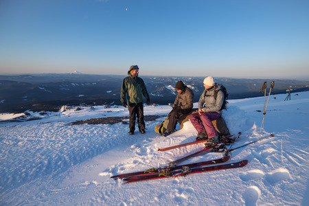 A group of friends conversing during a break while alpine touring in the mountains.