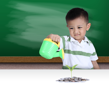 Little boy watering the small green plant growing out of coins