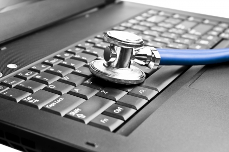 Stethoscope on black laptop computer