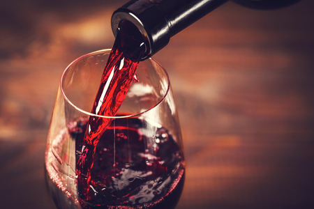 Photo pour Pouring red wine into the glass against wooden background - image libre de droit