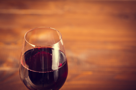 Red wine in wineglass against wooden background