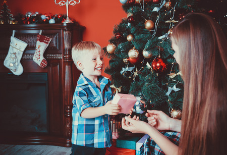 beautiful portrait of happy mother and son on the background of the Christmas tree in new year room with gifts. The idea for postcards. Soft focus. Shallow dof