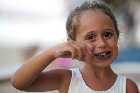 Photo pour Adorable 4 year old girl eating and smiling. - image libre de droit