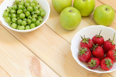 Photo for Top view of green apples, juicy red strawberries and sour gooseberries in white bowls on bright wooden table. Summer harvest background with copy space. Natural homegrown food. Place for custom text. - Royalty Free Image