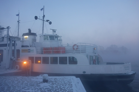 Helsinki, Finland - January 5, 2016 - Small passenger ferry MS Suokki waiting for departure at docks on Suomenlinna fortress island in midst of thick sea smoke or fog on extremely cold January winter morning at dawn in Helsinki, Finland on 5 January 2016.